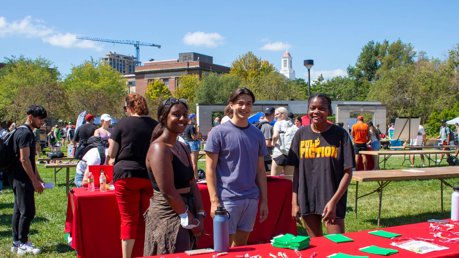 Three smiling students outside at Club Fair booth