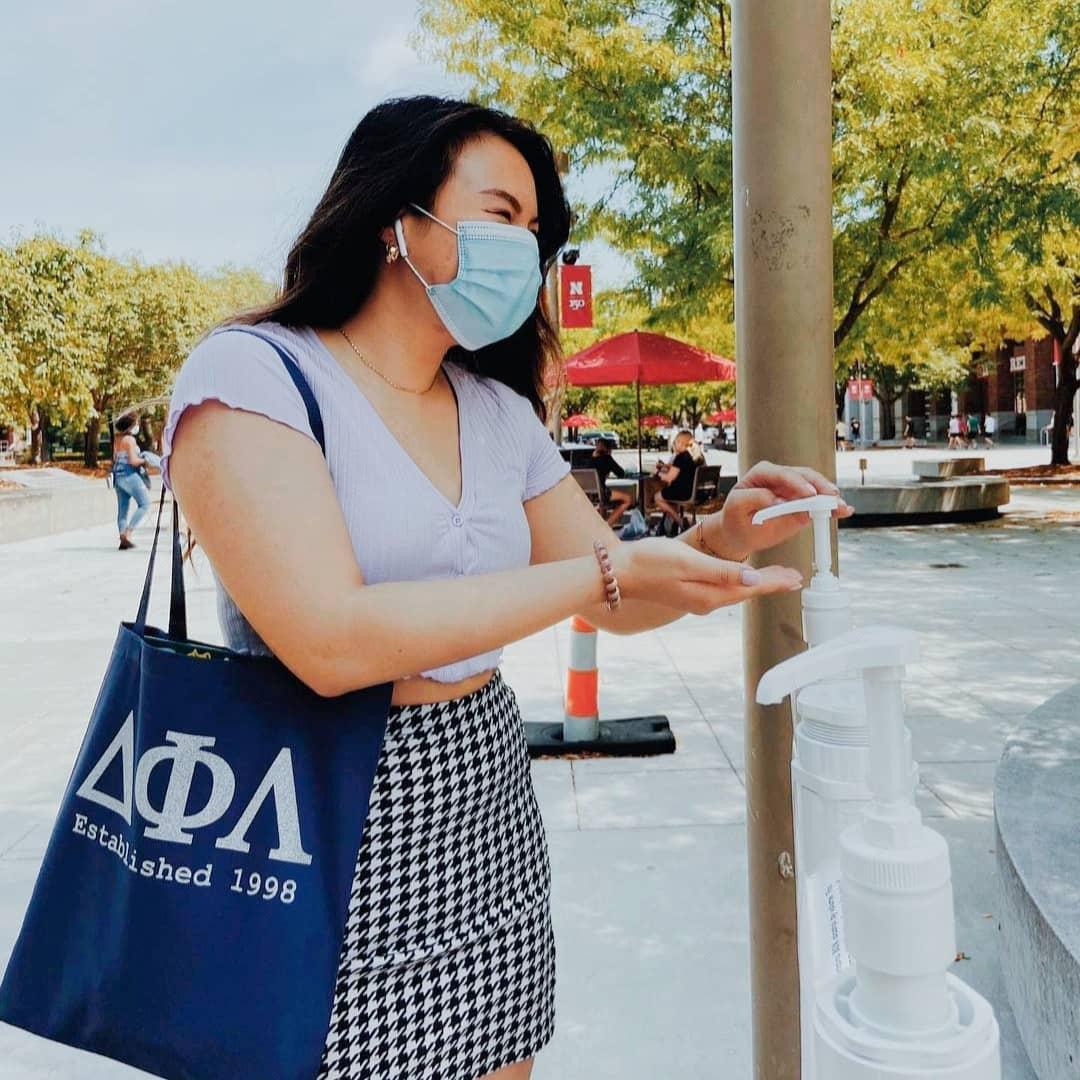 Delta Phi Lambda member uses hand sanitizer