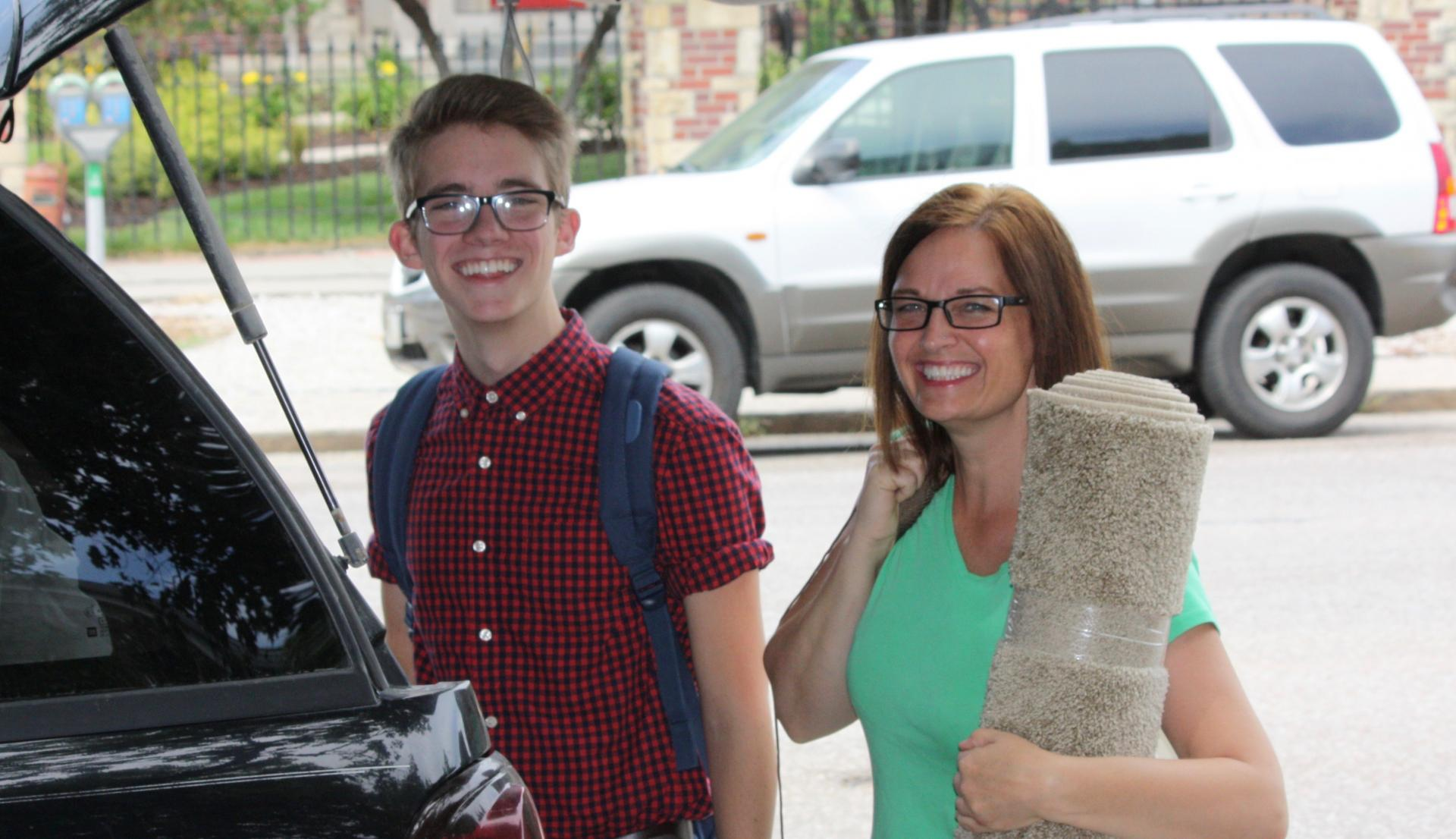A mother helps her son move into his residence hall