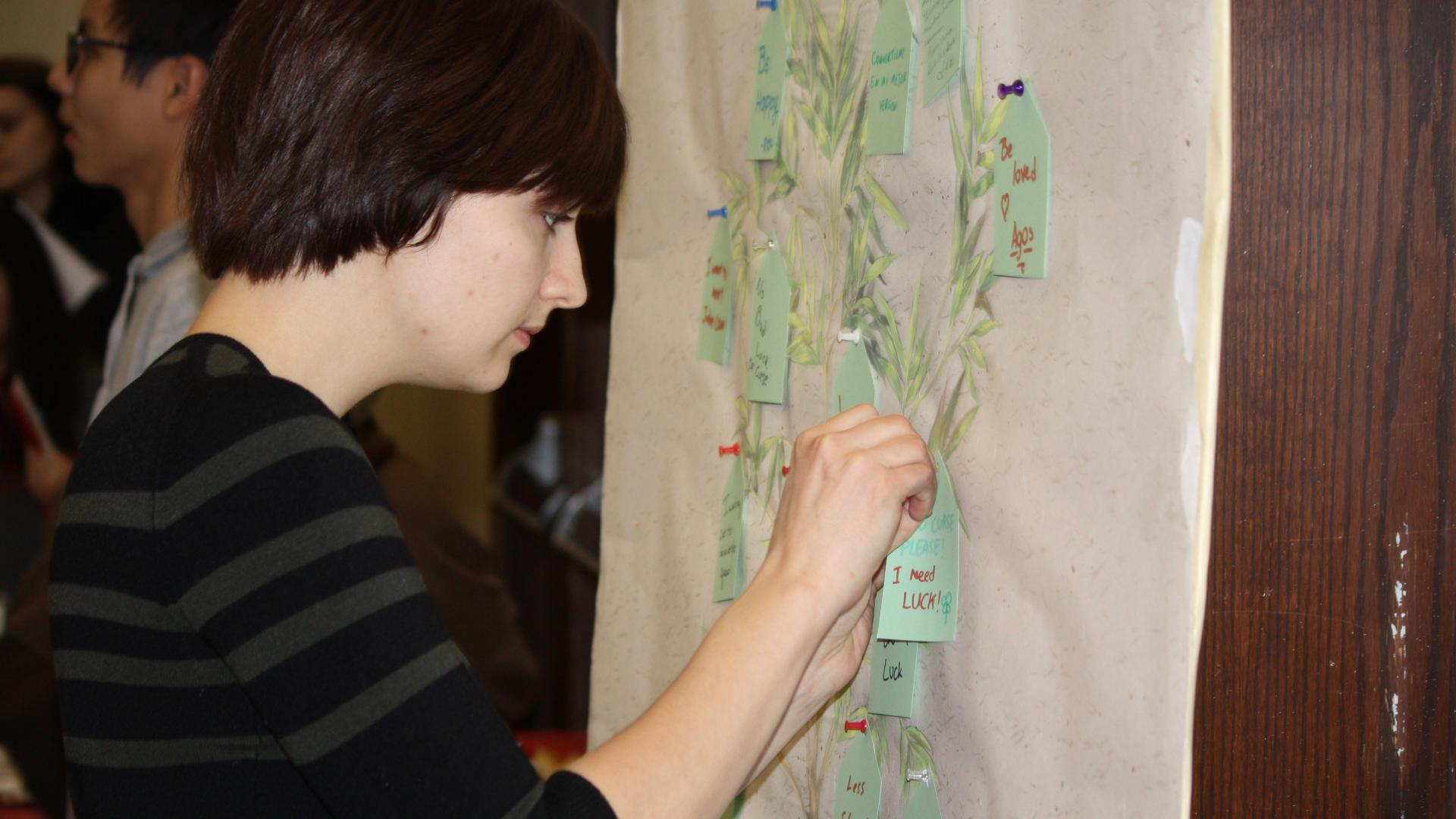 Student pins a note on a feedback board at a student event