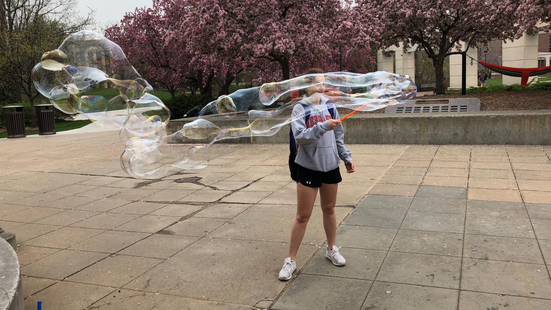 A student relaxes by blowing bubbles during finals week.