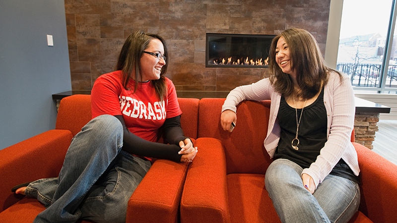 Two female students relax in front of a fireplace in the residence hall.