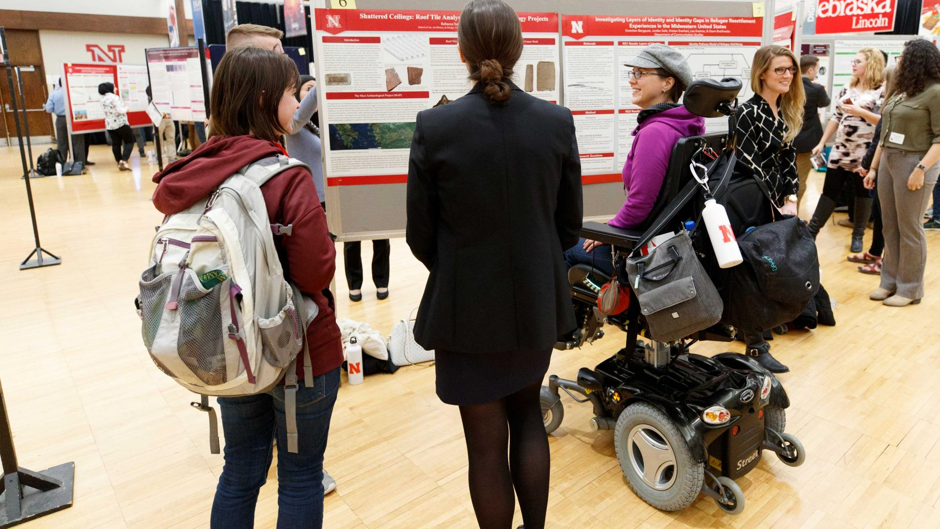 Two students standing and one student in a wheelchair analyze research posters