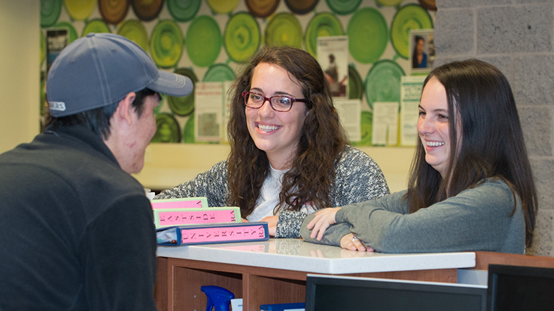 A desk assistant chats with RAs at the front desk of a residence hall