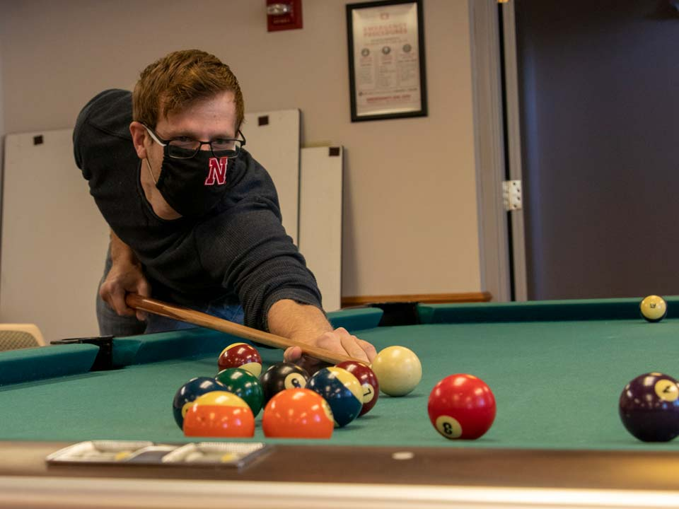 Jon Haag plays pool with friends during a game night following a Collegiate Recovery Community meeting at Husker Hall.
