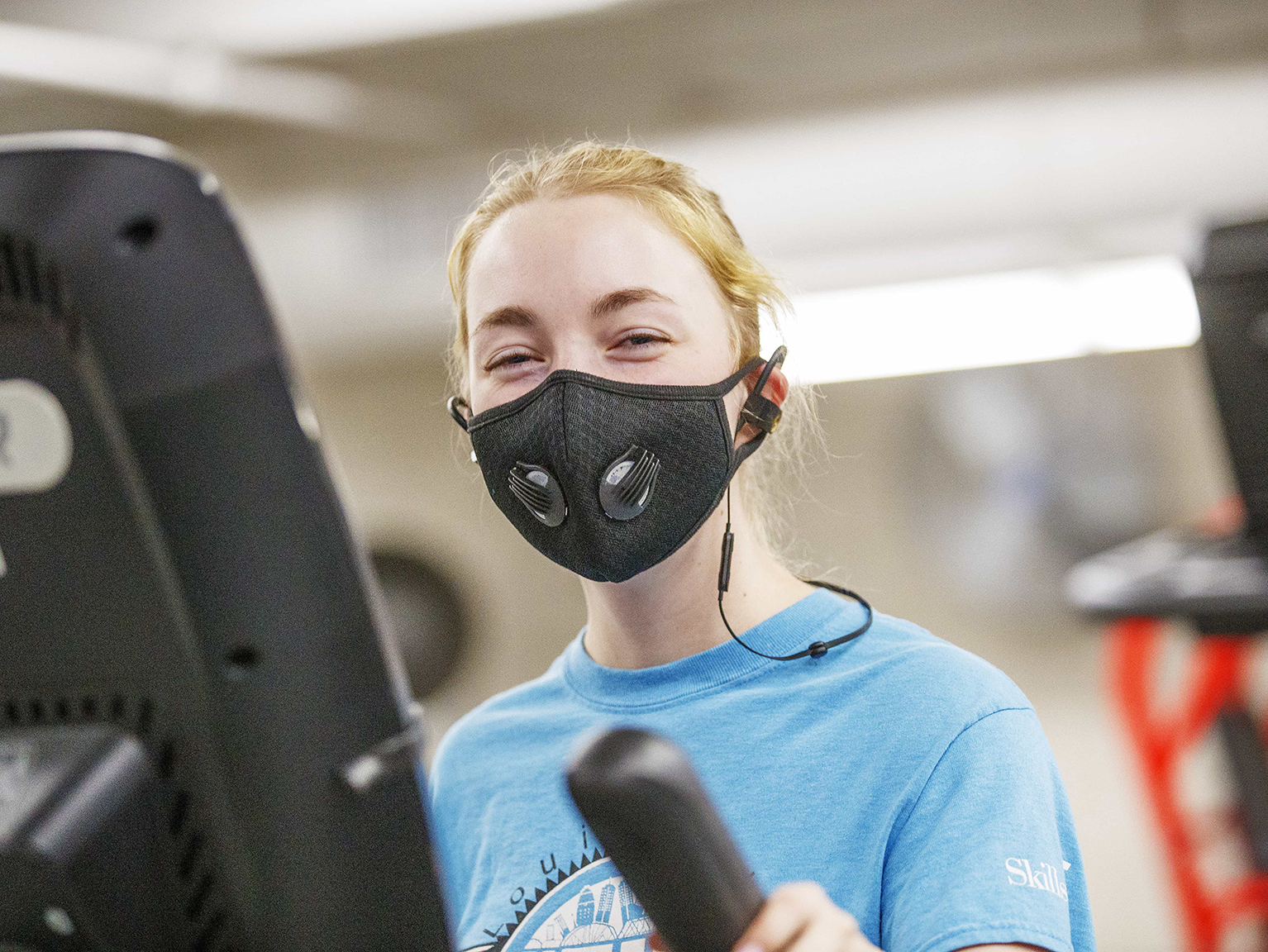 A student wears a black face covering while exercising in the Campus Rec Center's strength training & conditioning room.