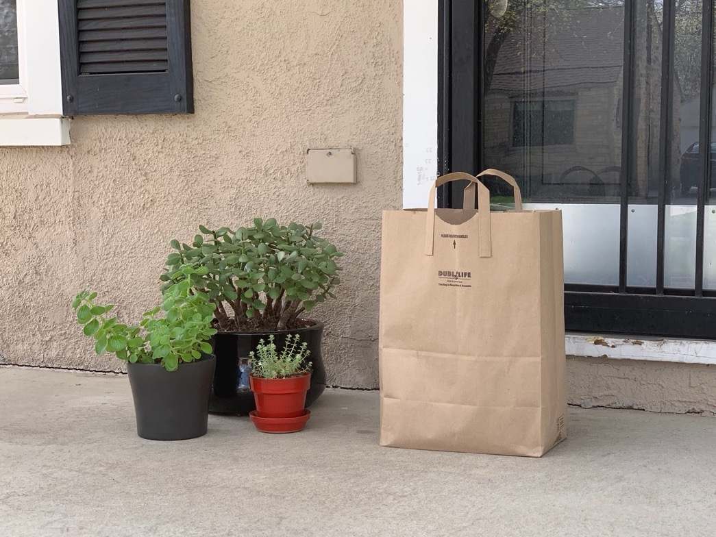 A paper grocery bag sits outside a house's door. (Christopher Dulak | UNL Student Affairs)