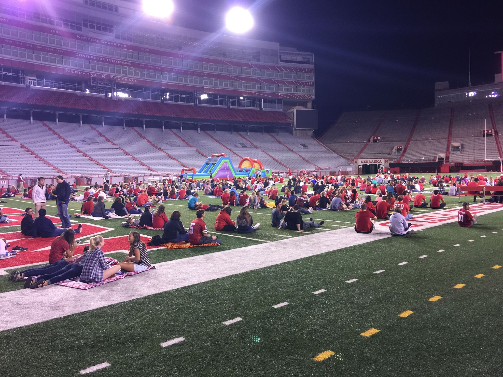 Students and UNL Family Weekend attendees on the field at the Husker Watch Party inside Memorial Stadium.