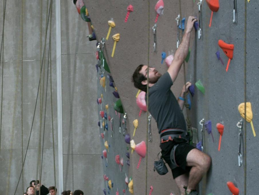 A climber scales teh climbing wall in the Outdoor Adventures Center.