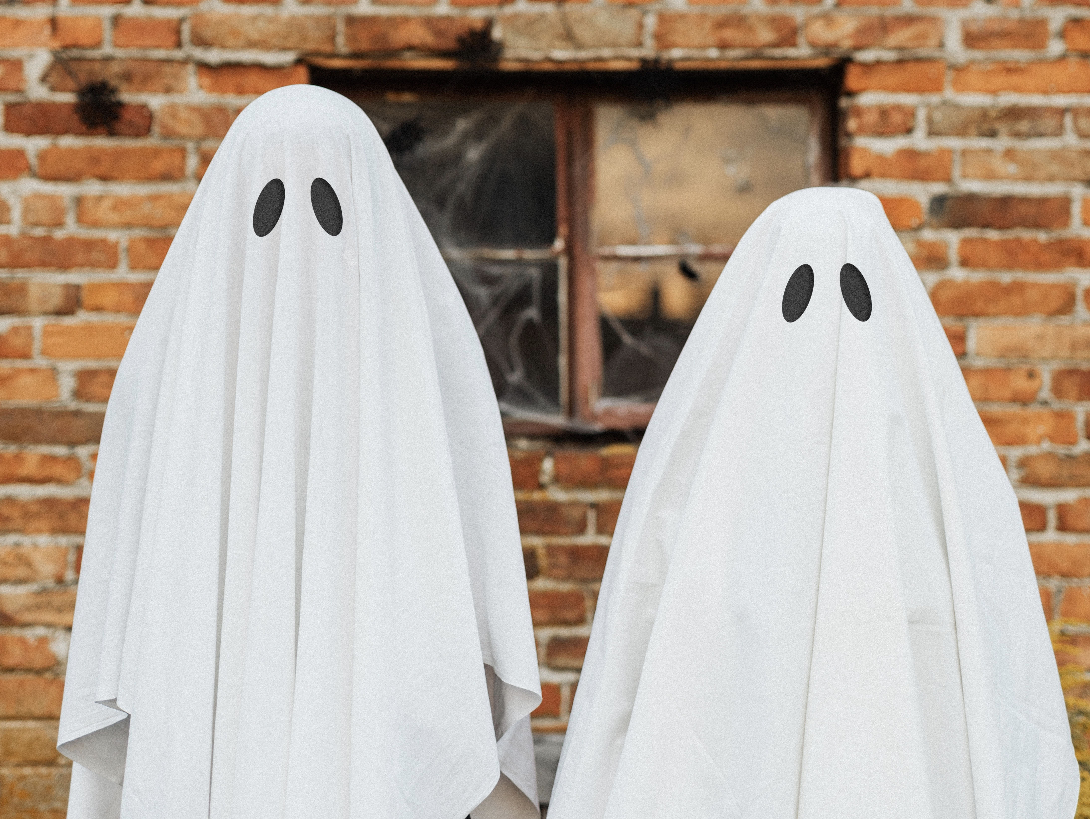 Two sheet-covered ghost costumes for Halloween.