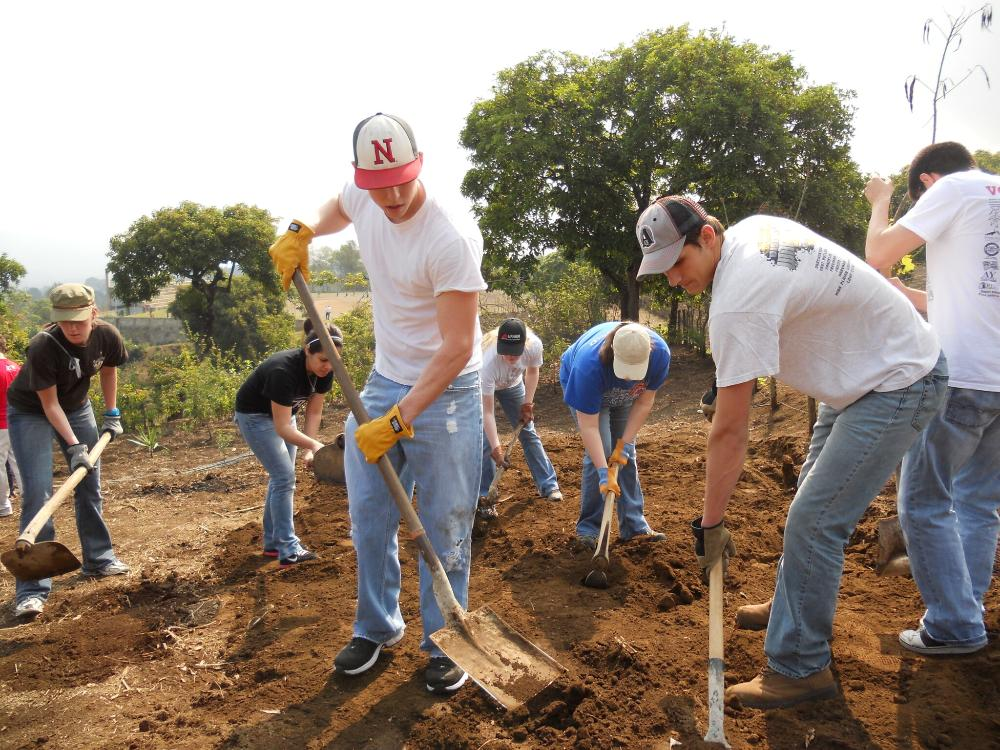 UNL students use shovels to move dirt at a house construction site.