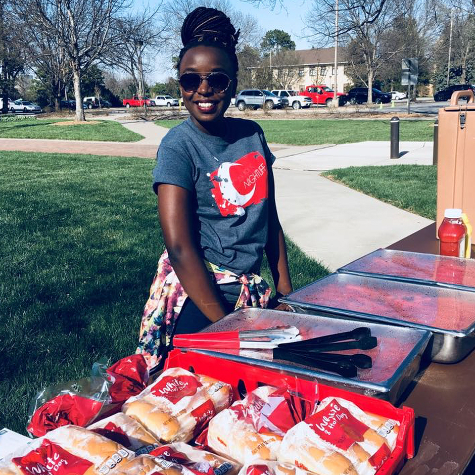 Student passes out hot dogs at End of Year Bash