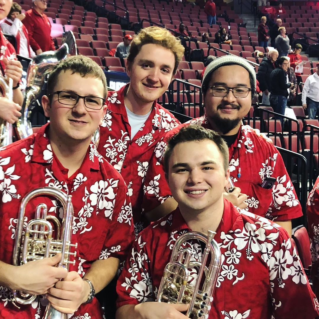 Four male students with floral print shirts hold mellophones