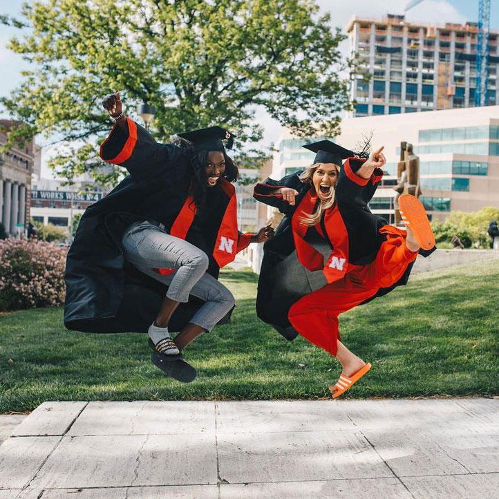 Two Nebraska students in graduation jump in air
