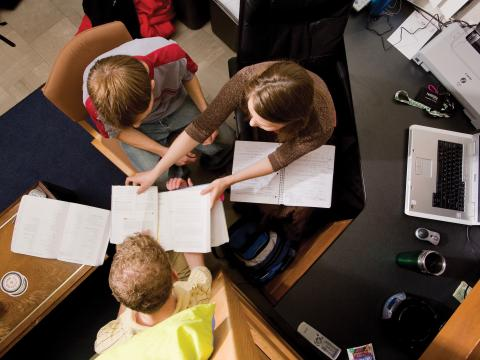 Three students study in residence hall.