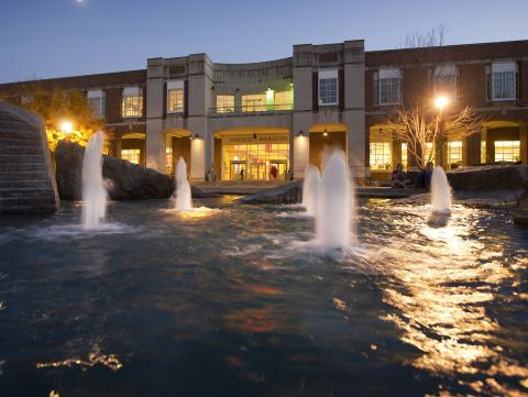 Broyhill Fountain at dusk, with Nebraska Union in the background.