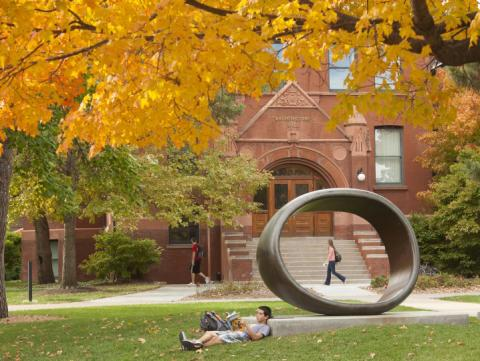 A male student reclines and reads a book in the Sheldon Museum of Art's Sculpture Garden under the golden colors of the autumn tree foliage.