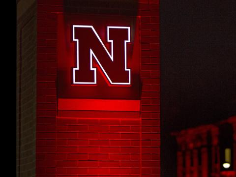 Glowing Nebraska N on brick pillar