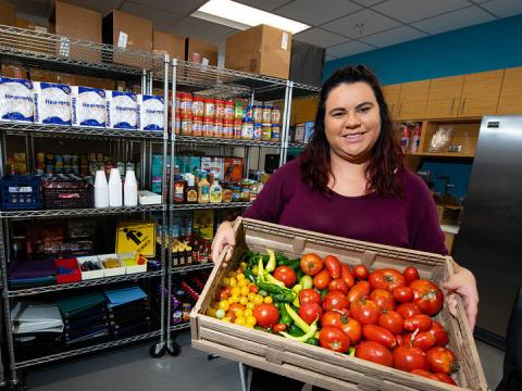 Morgan Smith, a graduate research assistant, shows a tote of fresh vegetables available at Husker Pantry. The pantry and Money Management Center is located in the University Health Center.