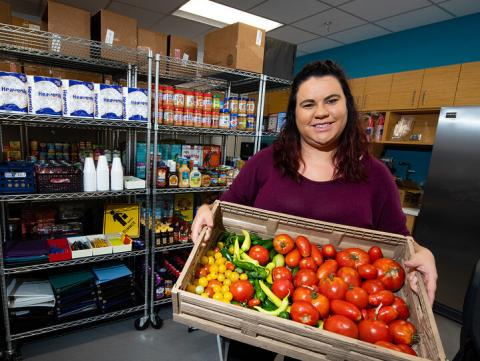 Graduate student Morgan Smith displays a tote of fresh vegetables available at the Husker Pantry. The on-campus food pantry helps more than 120 students per week secure free food and hygiene items.