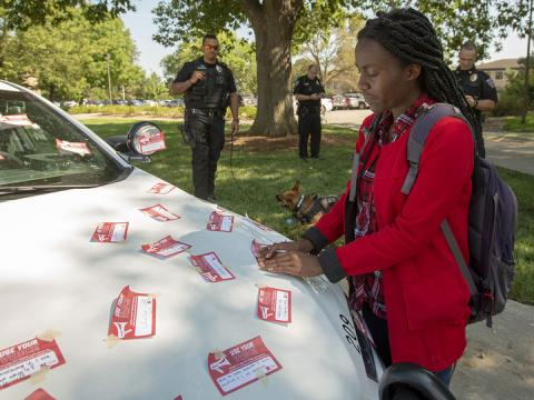"""Elizabeth Uwase, a junior integrated science major from Rwanda, affixes her """"Use Your Voice"""" pledge to a police car during the Sept 10 Cover the Cruiser event on East Campus. More than 75 students, faculty and staff made a pledge to stand up to sexual violence in the first day of the initiative."""