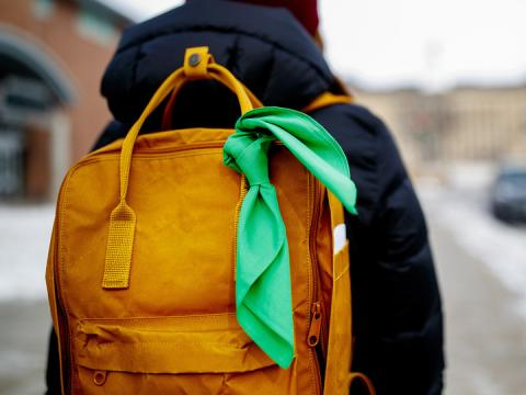 A student displays a green bandana tied to their backpack - a symbol of the Green Bandana project.