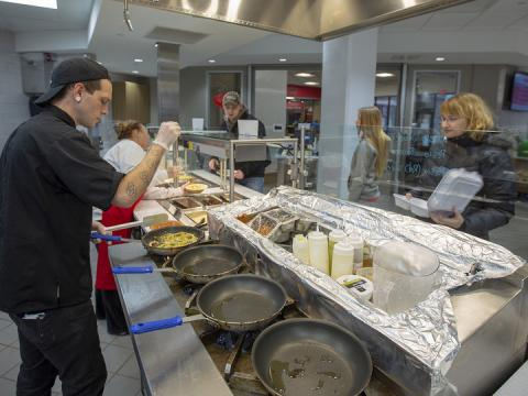 Samuel Klein, a dining service associate, prepares fresh fettuccine alfredo for Erin Bauer (right) at the World's Fare station in the new East Campus Dining Facility. The renovated space is part of a larger project that will offer three dining options in the Nebraska East Union.