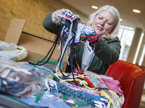 Veronica Riepe counts donated cloth masks before they're distributed to the nearly 1,000 university employees who continue to work on campus.