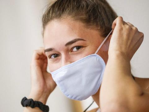 Olivia Boldt, senior from Madison, South Dakota, puts on her mask before going to work out in the Campus Recreation Center during 2020 summer sessions.