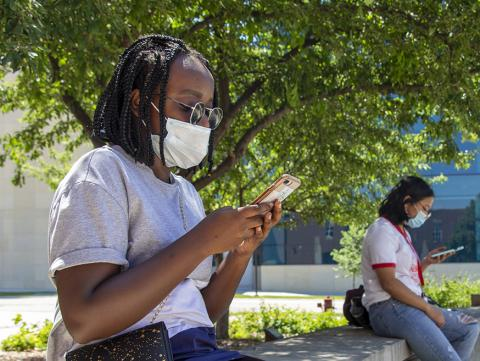 A black female student reads her smartphone outside the College of Education and Human Sciences building.