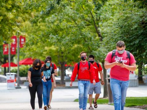 Students walk across campus while wearing face coverings