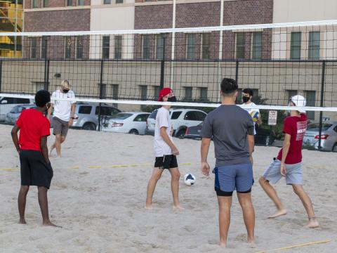 Students playing sand volleyball at the 18th & S Rec Area located north of Eastside Suites.
