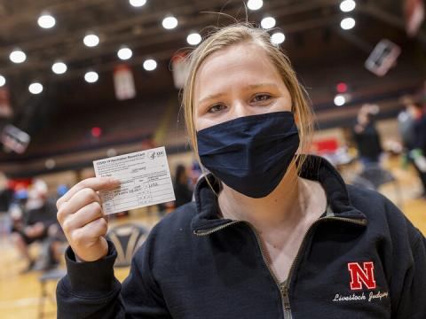 Student holds up vaccination card for COVID-19