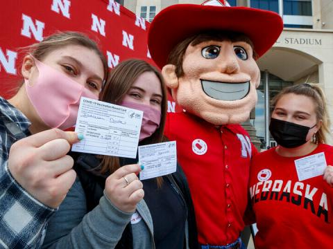 Husker students show their COVID-19 vaccination cards