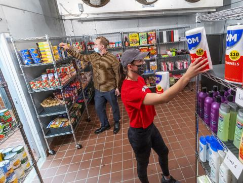 Morgan Berg (right), a senior in psychology from West Fargo, North Dakota, and Tim Anderson, a third-year law student from Huntington Beach, California, stock the shelves in the new East Campus Food Pantry. The pantry is in Filley Hall in the old Dairy Store walk-in freezer. [Craig Chandler | University Communication]