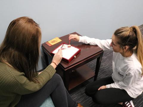 Two students play with a zen box.