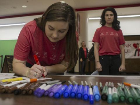Students create cards for military and veteran children as part of the Husker Civic Challenge.