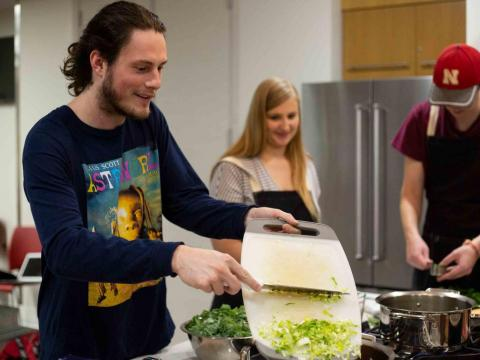 Sterling Dorton slides celery into a pot during the Zero Waste cooking class at the University of Nebraska-Lincoln Recreation & Wellness Center on East Campus in Lincoln, Nebraska on Thursday, Sept. 19, 2019.