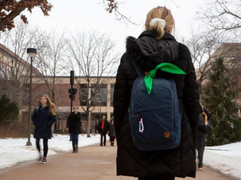 A female student walks across campus with a green bandana tied on her backpack.