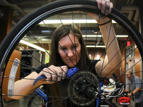 Female bicycle mechanic works on a tire inside the Outdoor Adventure Center's bike shop.
