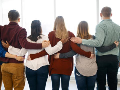 Students with hands on back show support for one another.