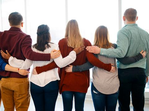 Students with arms behind backs showing support for one another.