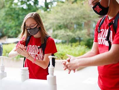 Students use hand sanitizer