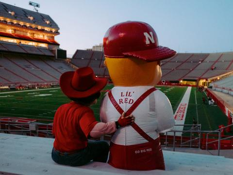 Herbie Husker and Lil' Red sitting in Memorial Stadium