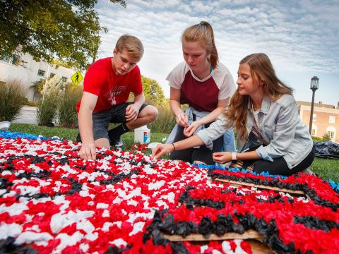 Students use napkins and glue to create lawn displays as part of the 2018 Homecoming festivities.