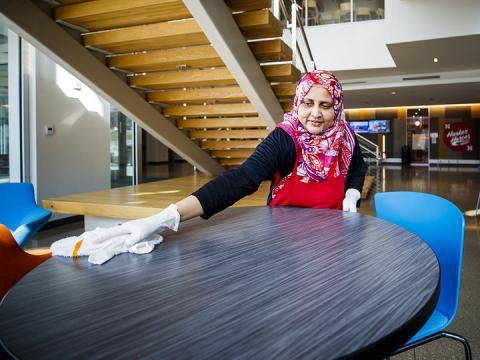 Kishuar Sultana, a University Dining Services employee, cleans tabletops in Nebraska's Willa S. Cather Dining Complex.