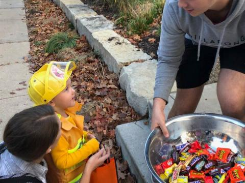 A child dressed as a firefighter selects candy.