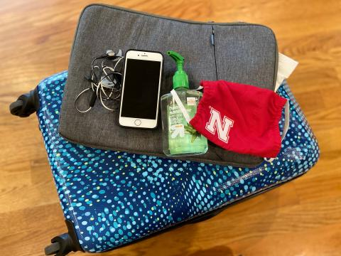 Phone, hand sanitizer, mask, suitcase -- ready for travel