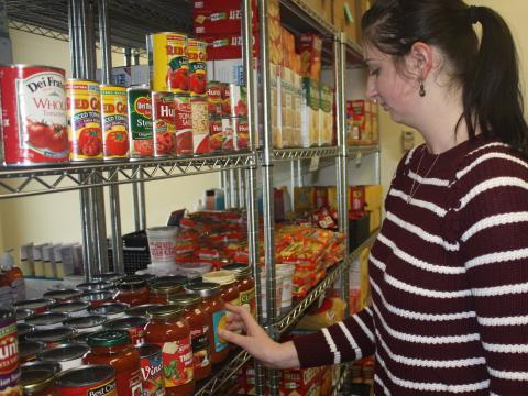 Jessica Lanctot, graduate assistant in the Huskers Helping Huskers Pantry+ adds donated pasta sauce to the pantry shelf.