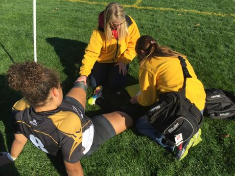 Two athletic training students with the Injury Prevention & Care program assess an injury on a female soccer player.
